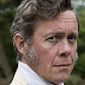Reverend Hutton played by Alex Jennings (i)